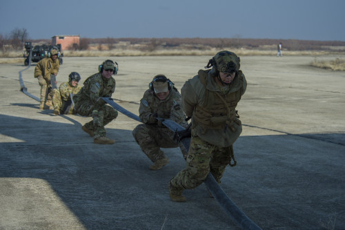Airmen clear remaining fuel in a hose back into an MC-130J Commando II, assigned to the 67th Special Operations Squadron, during forward area refueling point training at Plovdiv, Bulgaria, Feb. 9, 2016. The C-130 can provide fuel to multiple aircraft in the air or on the ground with the FARP team. (U.S. Air Force photo by Airman 1st Class Luke Kitterman/Released)