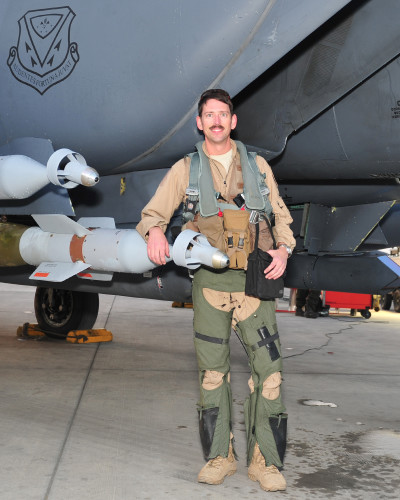 Lt. Col. Bash, 391st Expeditionary Fighter Squadron weapons system officer and instructor, poses for a photo with an F-15E Strike Eagle fighter aircraft after returning from his 1,000 combat flying hour milestone sortie at undisclosed location in Southwest Asia, April 9, 2016. The 1,000 hour milestone, an equivalent to more than 40 days in combat, is lauded as a rare achievement, which some flyers never achieve. (U. S. Air Force photo by Staff Sgt. Kentavist P. Brackin/Released)