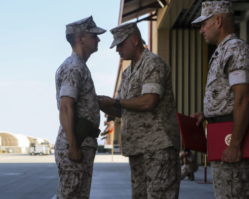 Lt. Col. William Maples is presented a Meritorious Service Medal during a re-designation and change of command ceremony aboard Marine Corps Air Station Yuma, Ariz., June 30. During the ceremony, Marine Attack Squadron (VMA) 211 transitioned to Marine Fighter Attack Squadron (VMFA) 211 making it the first AV-8B Harrier squadron to become an F-35B Lightning II Joint Strike Fighter squadron. (U.S. Marine Corps photo by Lance Cpl. Harley Robinson/Released.)