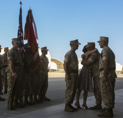 Lt. Col. William Maples' wife is congratulated after receiving a certificate of appreciation during a re-designation and change of command ceremony aboard Marine Corps Air Station Yuma, Ariz., June 30. During the ceremony, Marine Attack Squadron (VMA) 211 transitioned to Marine Fighter Attack Squadron (VMFA) 211 making it the first AV-8B Harrier squadron to become an F-35B Lightning II Joint Strike Fighter squadron. (U.S. Marine Corps photo by Lance Cpl. Harley Robinson/Released.)
