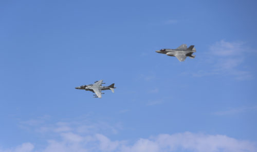 An AV-8B Harrier and an F-35B Lightning II Joint Strike Fighter conduct a flyover during a re-designation and change of command ceremony aboard Marine Corps Air Station Yuma, Ariz., June 30. During the ceremony, Marine Attack Squadron (VMA) 211 transitioned to Marine Fighter Attack Squadron (VMFA) 211 making it the first Harrier squadron to become an F-35 squadron. (U.S. Marine Corps photo by Lance Cpl. Harley Robinson/Released.)