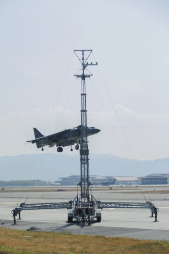 A U.S. Marine Corps AV-8B Harrier with Marine Attack Squadron (VMA) 542 performs a vertical landing while using the lights on the mobile Expeditionary Hover Position Indicator to adjust its position at Marine Corps Air Station Iwakuni, Japan, Aug. 9, 2016. VMA-542 is home based out of Marine Corps Air Station Cherry Point, N.C., and is forward deployed to MCAS Iwakuni, Japan, as part of the unit deployment program. The Harrier pilots used the mobile EHPI in coordination with Aircraft Recovery assigned to Headquarters and Headquarters Squadron to recertify on boat-deck landings to prepare for other future operations in the Pacific. (U.S. Marine Corps photo by Lance Cpl. Donato Maffin)