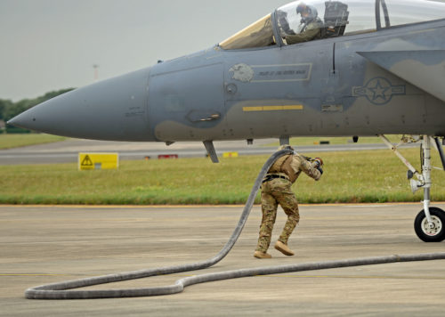 U.S. Air Force Airman 1st Class Sequan Gill, 100th Logistics Readiness Squadron forward arming and refueling point technician runs out a fuel hose to an F-15C Eagle from RAF Lakenheath July 26, 2017, on RAF Mildenhall, England. A FARP allows for aircraft to be able to rearm and refuel at an austere location and return to the mission without having to land at an actual base. (U.S. Air Force photo by Airman 1st Class Luke Milano)