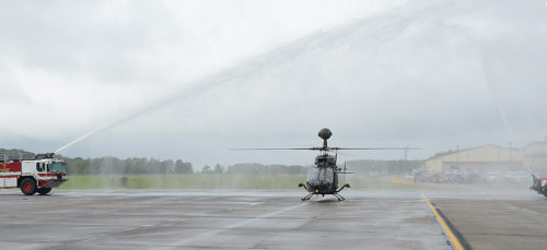 "An OH-58D ""Kiowa Warrior"" passes through water from fire trucks after its final flight at Joint Base Langley-Eustis, Va., Sept. 18, 2017. As part of the Army's Aviation Restructure Initiative, the Army began divesting the aircraft in 2014. (U.S. Air Force photo by Staff Sgt. Teresa J. Cleveland)"