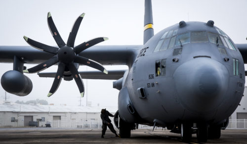 A 153rd Airlift Wing maintainer places chocks on the wheels of a C-130H after arriving at Eglin Air Force Base, Fla., Jan. 11. Air Force's first fully upgraded C-130H is here for test and evaluation on its new modified propeller system and engines. (U.S. Air Force photo/Samuel King Jr.)