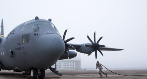 A 153rd Airlift Wing maintainer pulls a generator cable toward a C-130H after arriving at Eglin Air Force Base, Fla., Jan. 11. Air Force's first fully upgraded C-130H is here for test and evaluation on its new modified propeller system and engines. (U.S. Air Force photo/Samuel King Jr.)